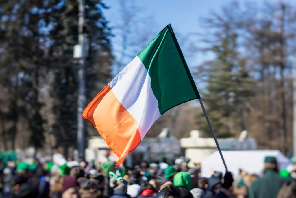 Flag of Ireland close-up in hands on background of blue sky during the celebration of St. Patrick's Day