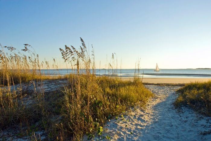 A sand pathway leads to the beach with a sailboat in the background on Hilton Head Island, SC.