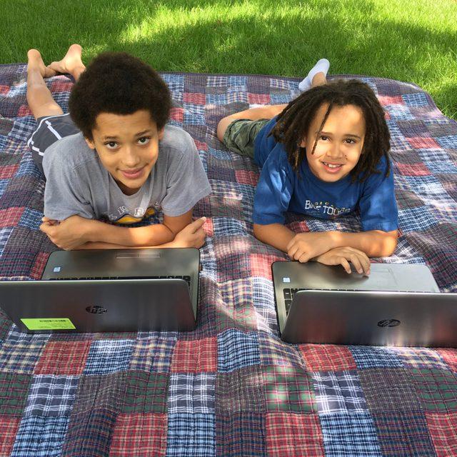 homeschooling. laptops on a picnic blanket outside.