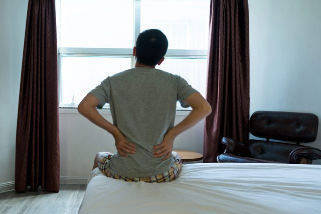 Man sitting on the edge of bed with backache
