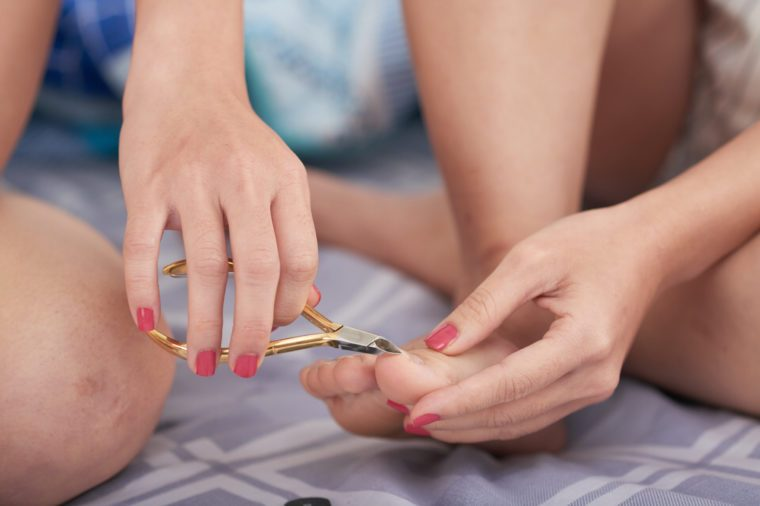 Crop woman cutting toenails