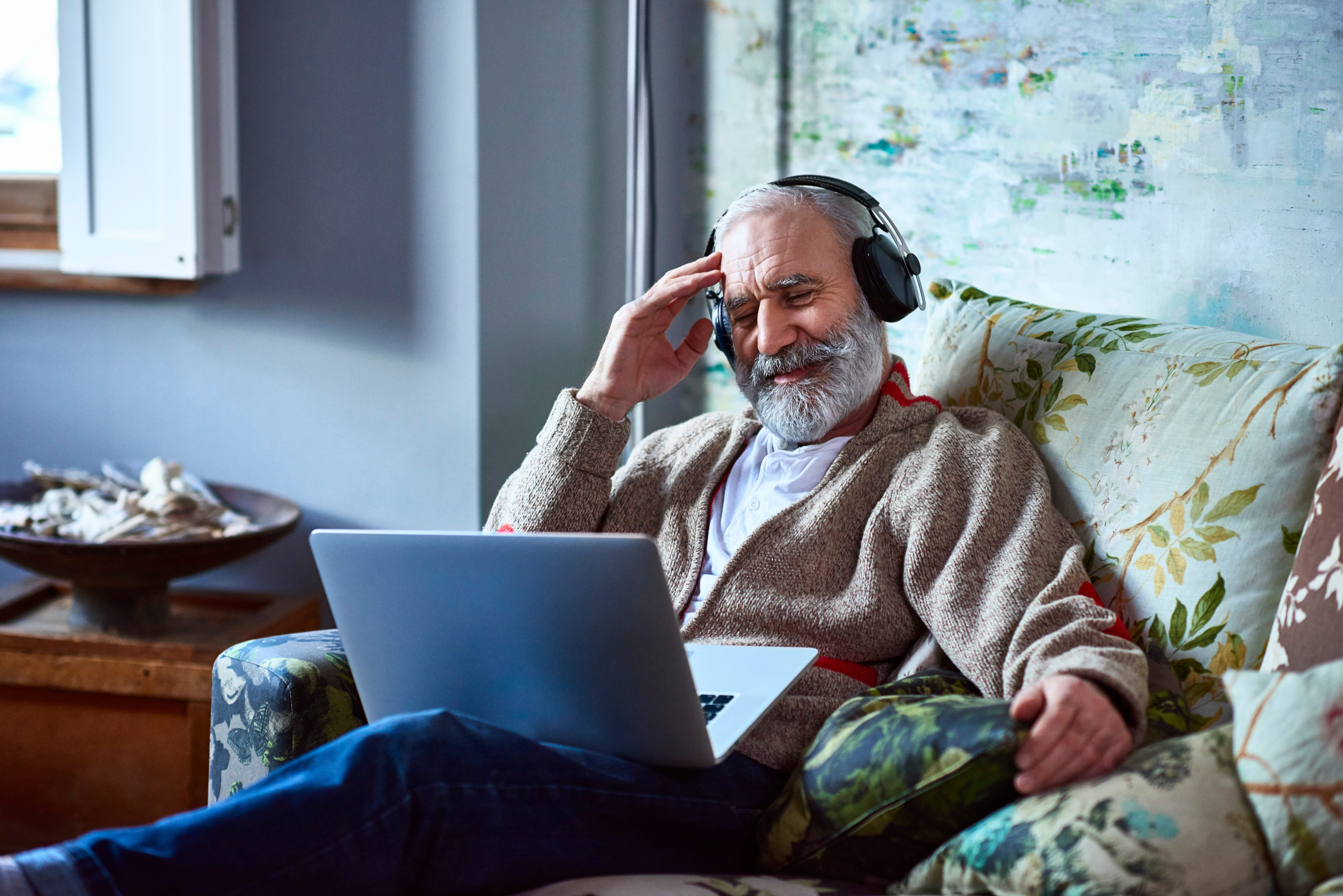 Portrait of mature man streaming movie on laptop wearing headphones