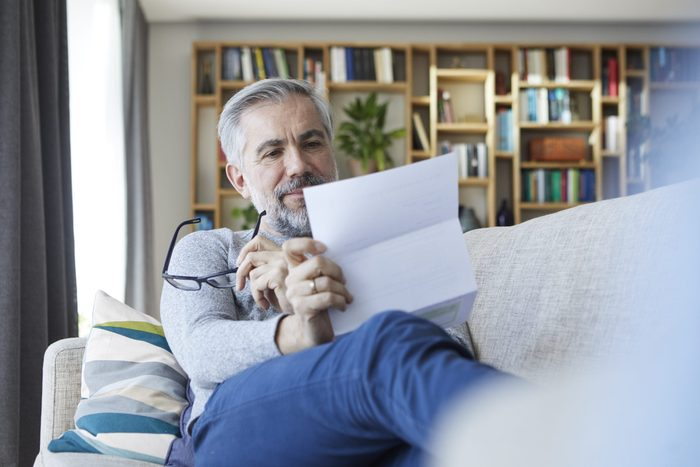 Mature man sitting on couch at home reading letter