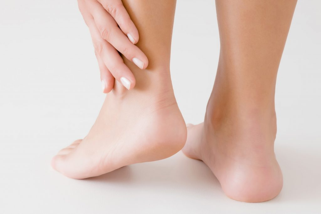 Young woman's hand touching perfect groomed legs on gray background. Tired feet. Care about clean, soft, smooth skin. Closeup. Back view.
