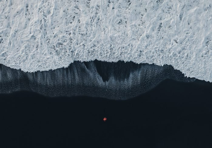 Aerial view of woman on black sand beach in Iceland