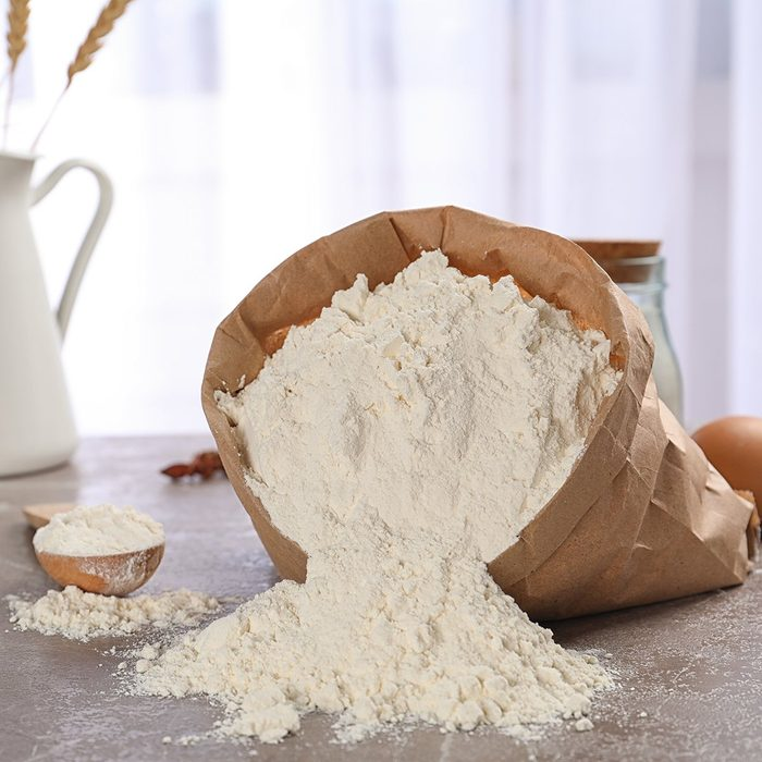 Paper bag and spoon with flour on table