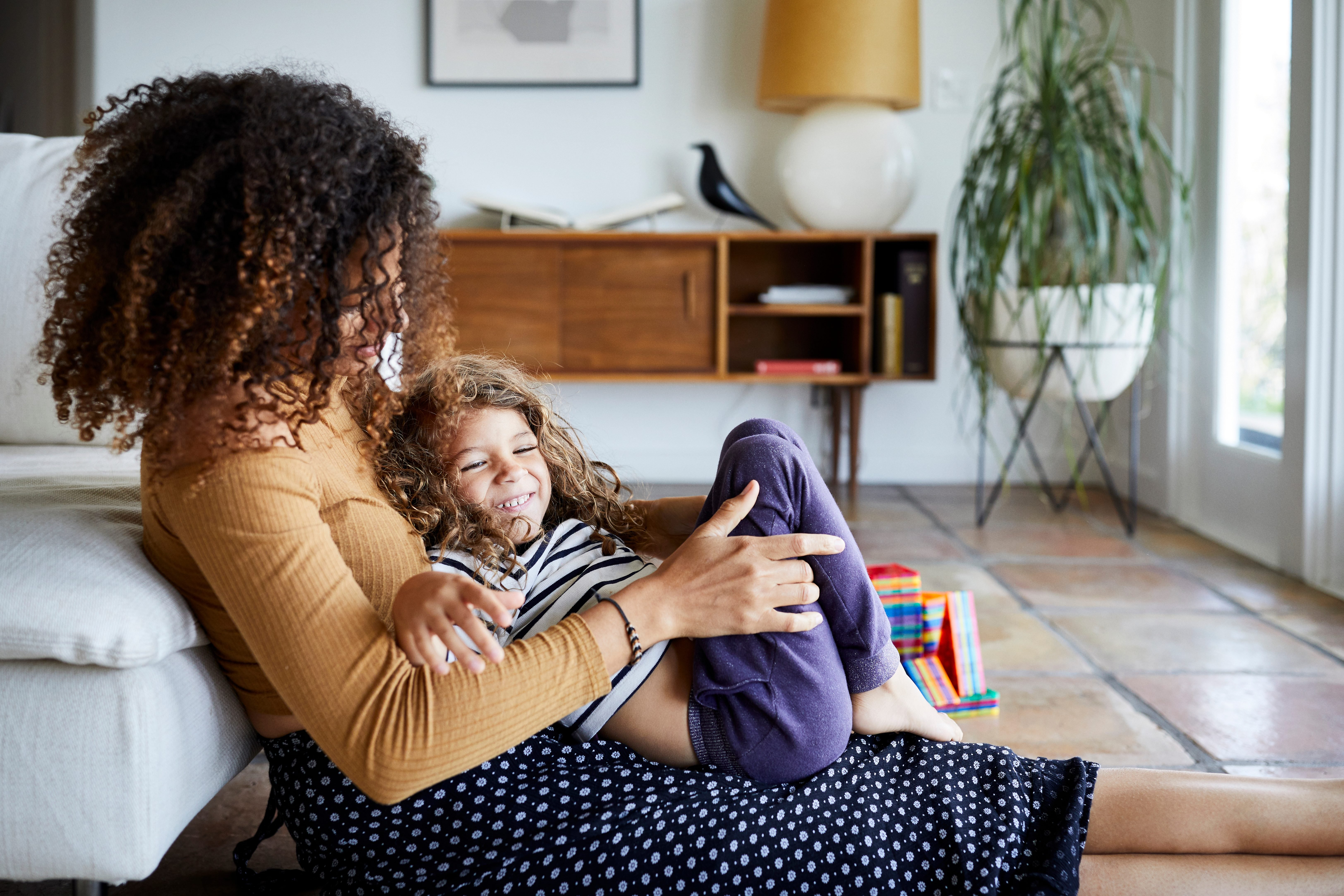 Happy mother playing with daughter while sitting on floor by sofa at home
