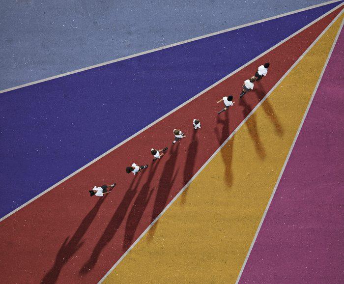 School children in uniforms walking in row on multi coloured background