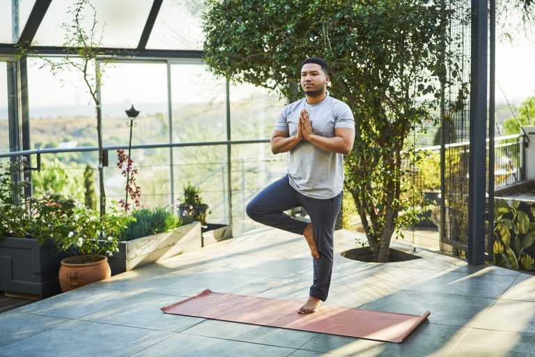 man practicing yoga outside at home