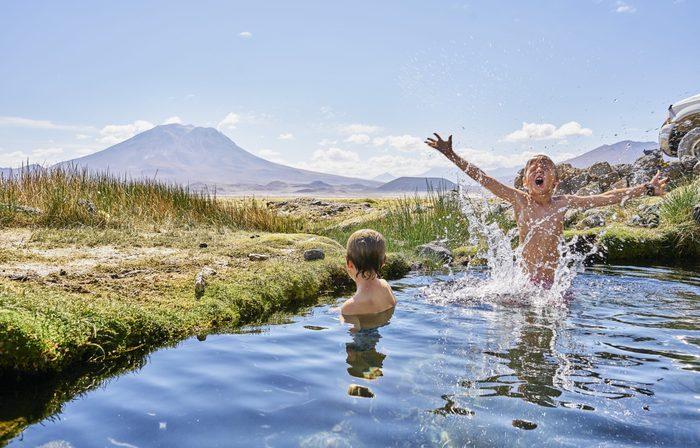 Chile, Salar del Carmen, two boys bathing in hot spring