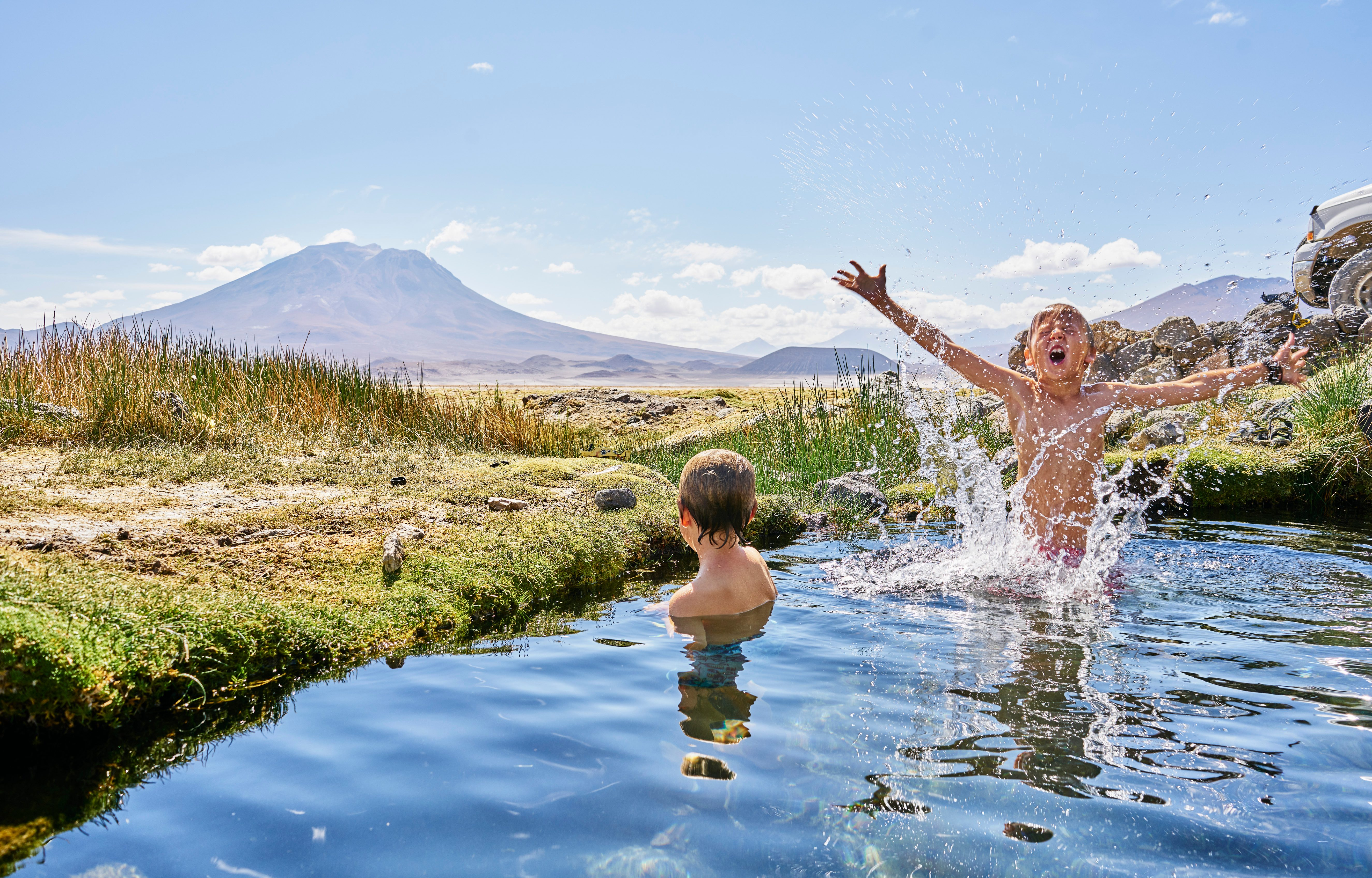 Chile, Salar del Carmen, two boys bathing in hot spring