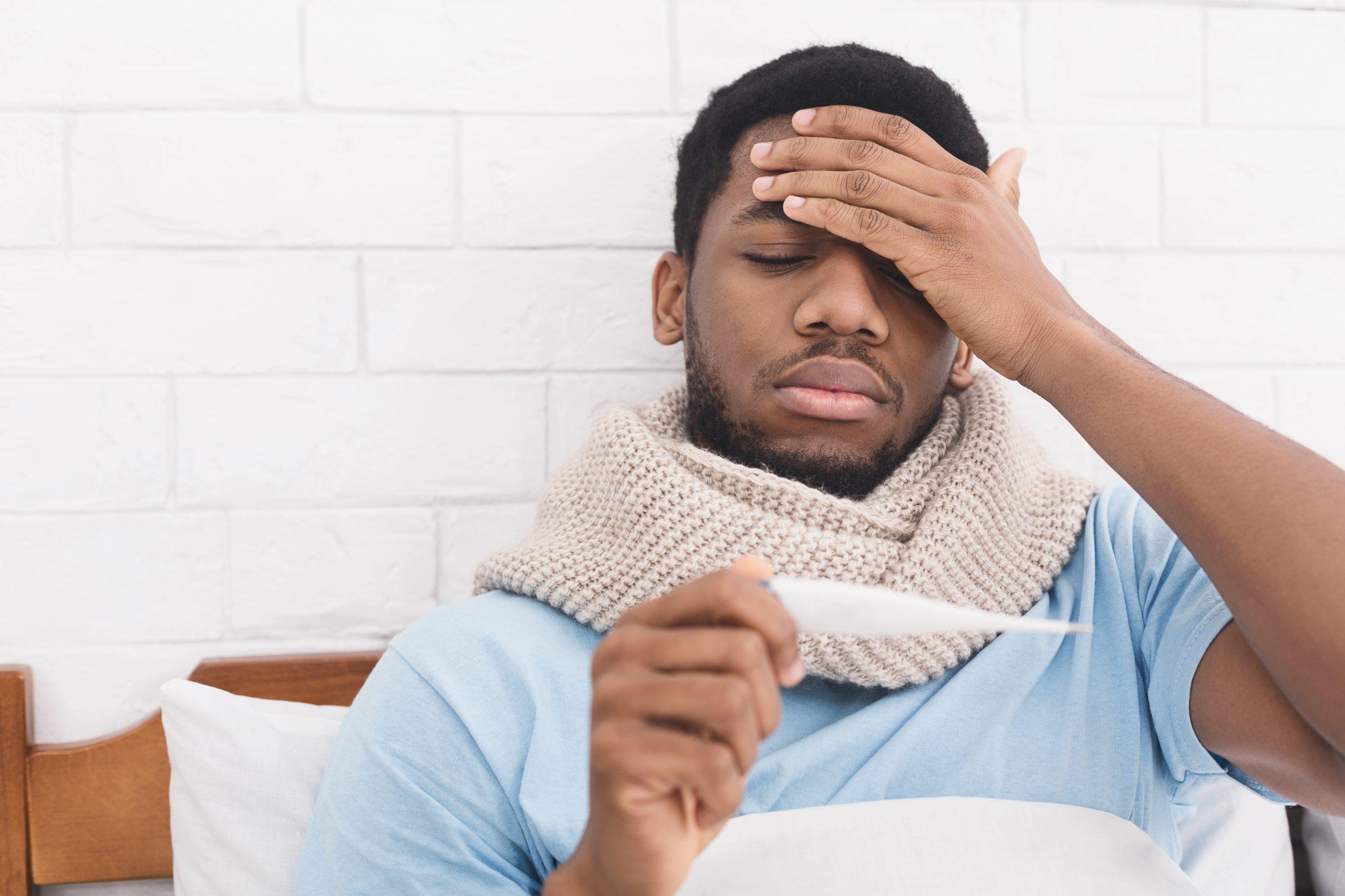 Sick african-american man measuring body temperature in bed