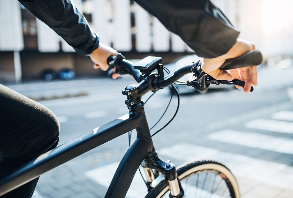 A midsection of businessman commuter with electric bicycle traveling to work in city.