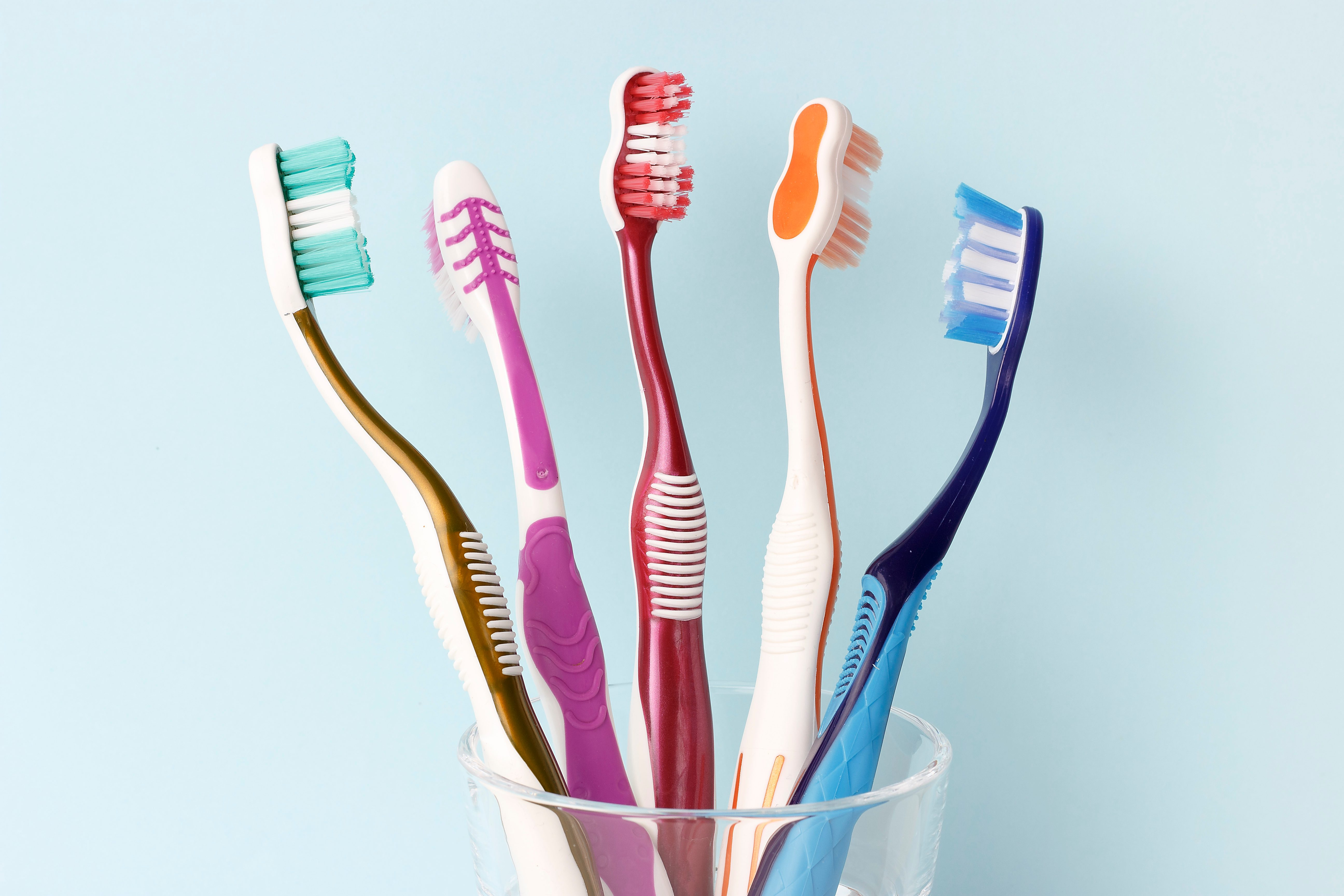 Multicolored toothbrushes in a glass cup front view, blue background
