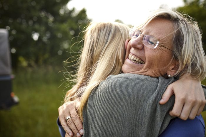 Happy senior woman and young woman hugging outdoors with a jeep in background
