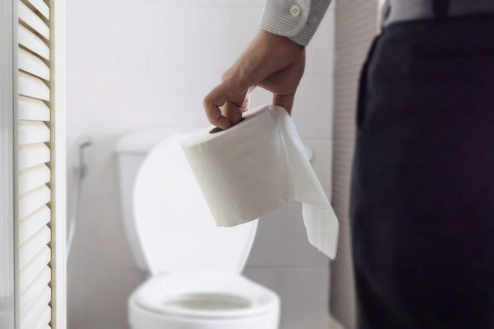 Midsection Of Man Holding Toilet Paper While Standing In Bathroom At Home