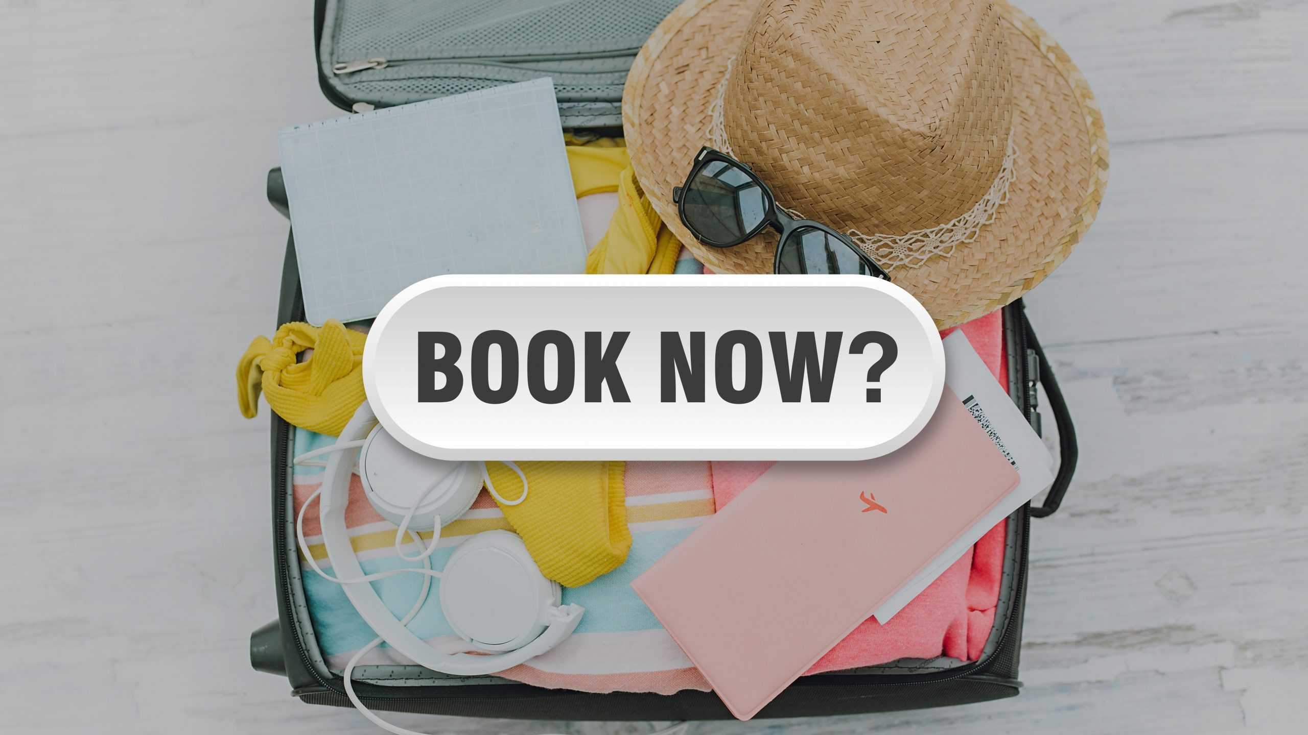 book now? button over packed suitcase background