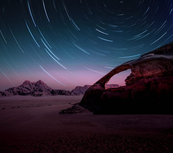 Long exposure of the stars in the Wadi Rum desert of Jordan with natural arch.