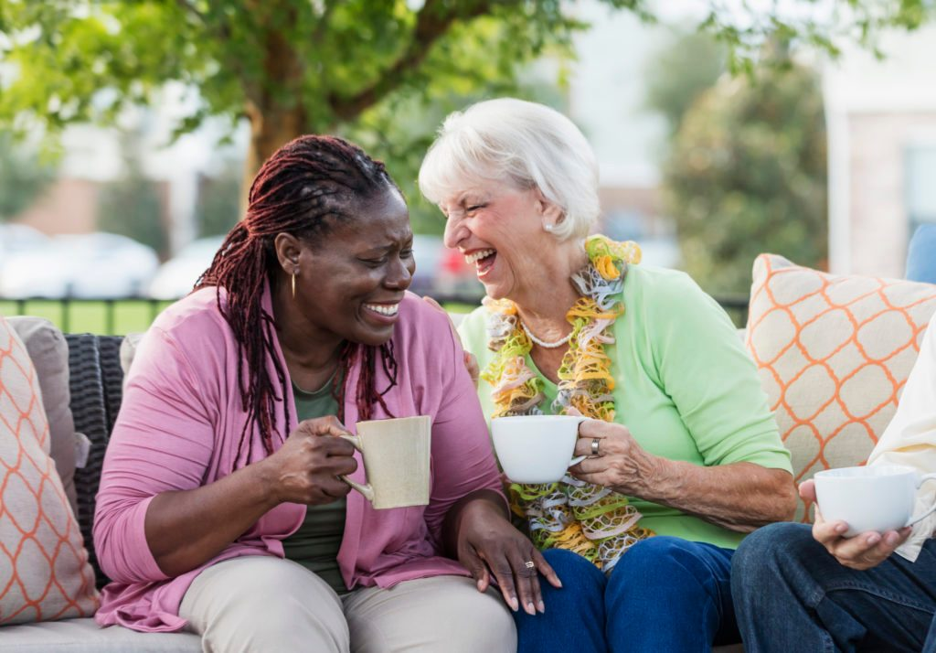Senior woman, African-American friend laughing together