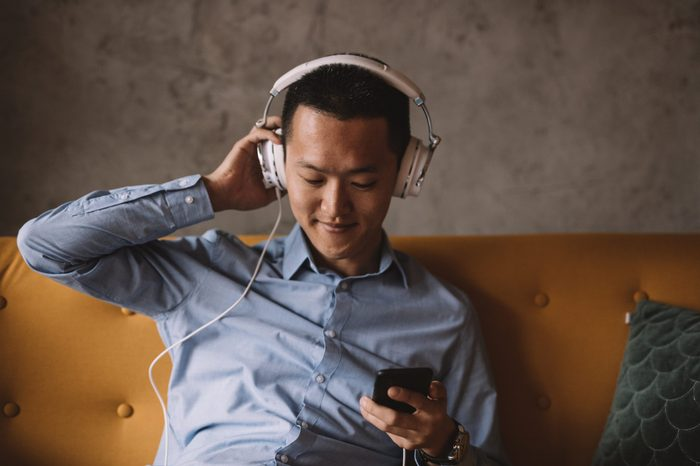 Young Asian man listening to music and relaxing in his office