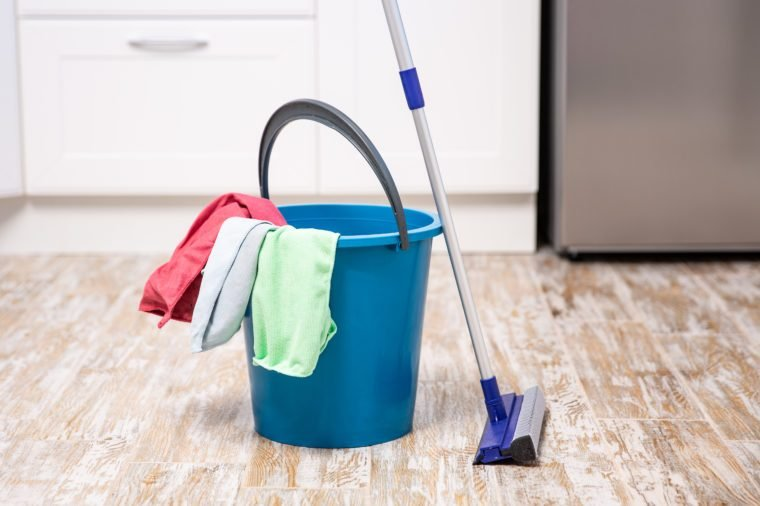 Plastic bucket with cleaning supplies in home