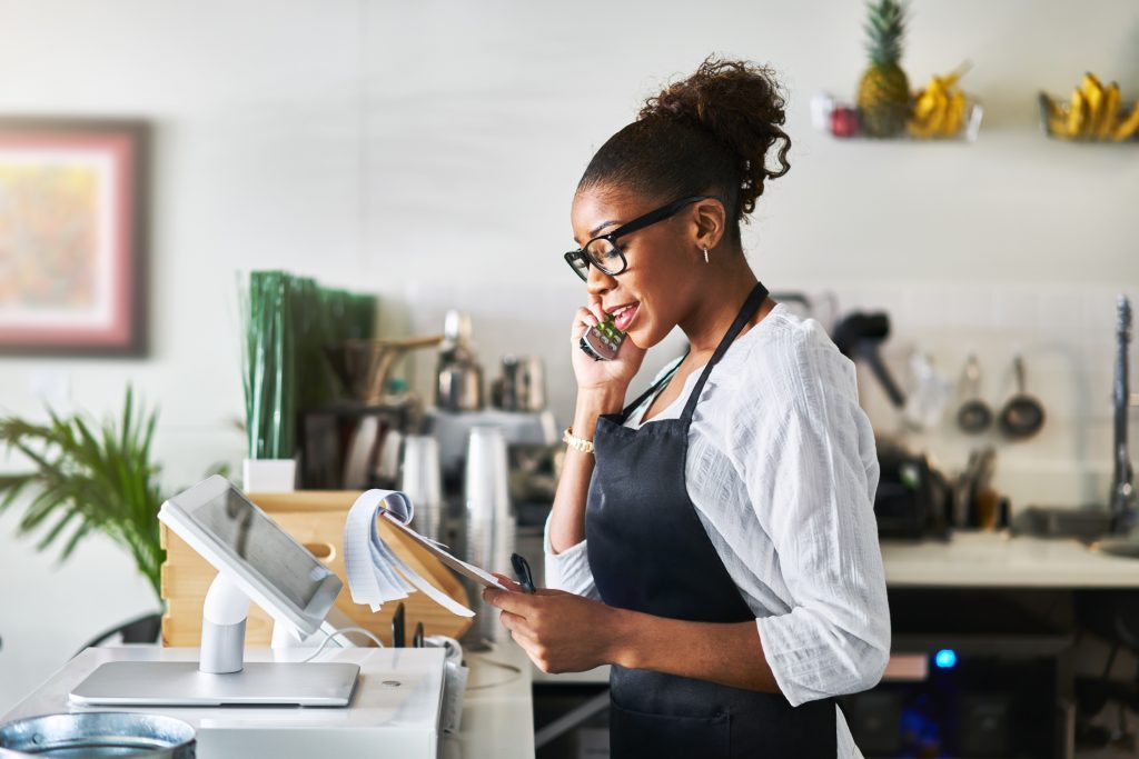 friendly waitress taking order on phone at restaurant and writing on notepad