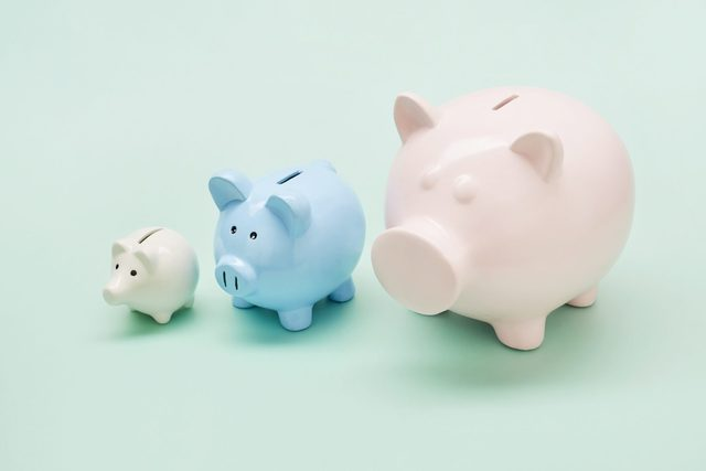 Still life of differently sized pink, blue and white piggy banks in ascending size order on turquoise background