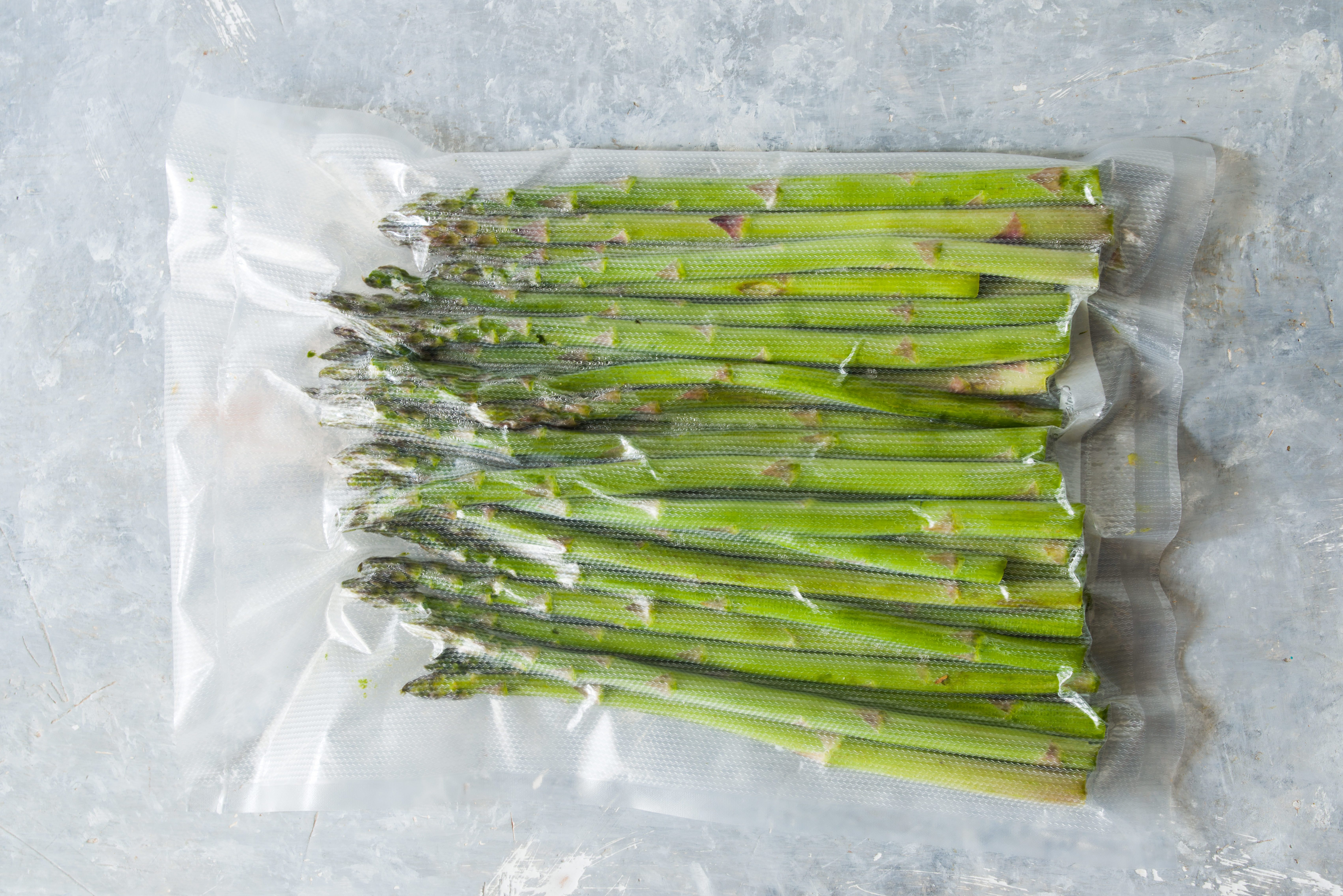 Vacuum sealed vegetables , asparagus, on a gray background top view, ready to be cooked with sous vide rooner