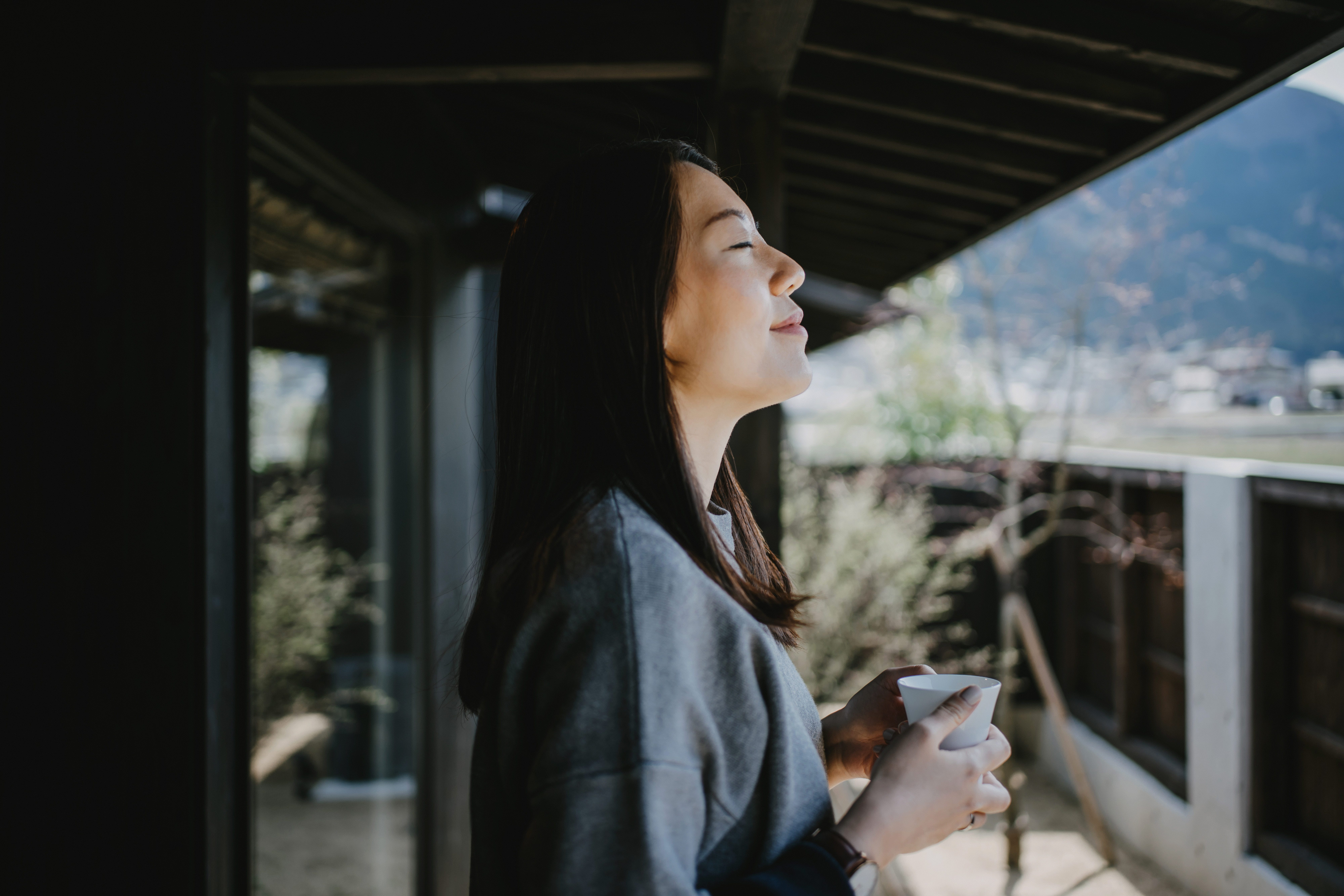 Beautiful young Asian woman drinking coffee and enjoying fresh air on balcony in the morning
