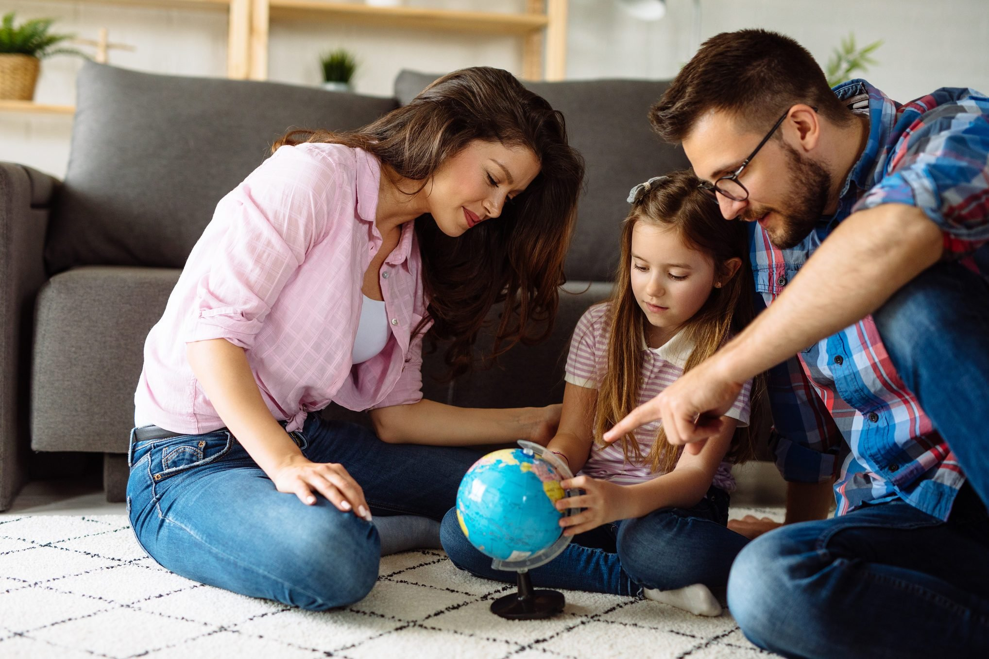 Parents and daughter looking at globe in living room