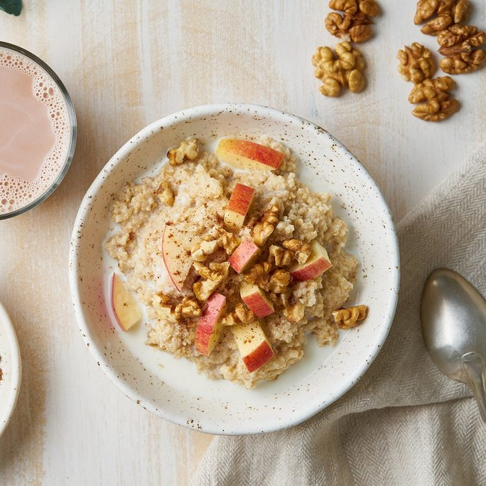 Oatmeal with apple, nuts, honey and cup of chocolate on white wooden light background. Top view. Healthy diet breakfast