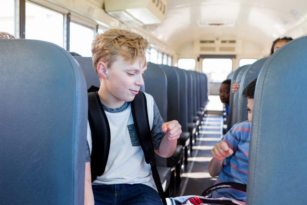 Friends fist bump on school bus