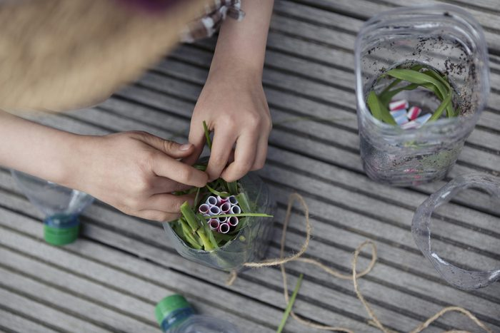 Child (6-7) using recycled plastic straws and bottles to repurpose into an insect house