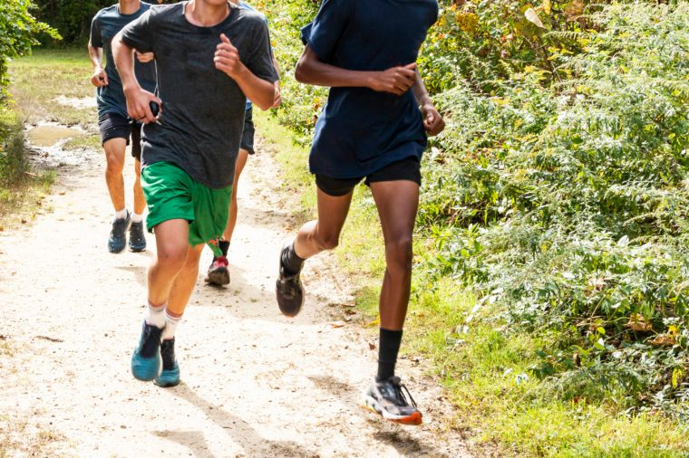 Group of high school boys running on a path