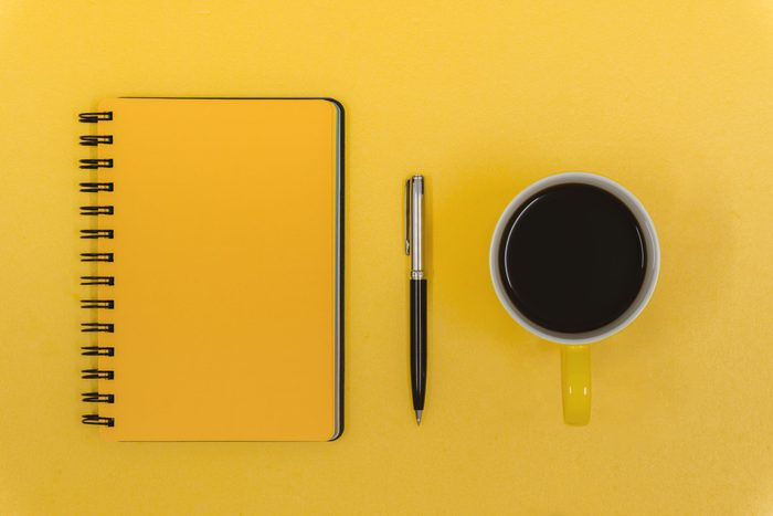 Notepad, Pen and Coffee Mug on Yellow Work Desk