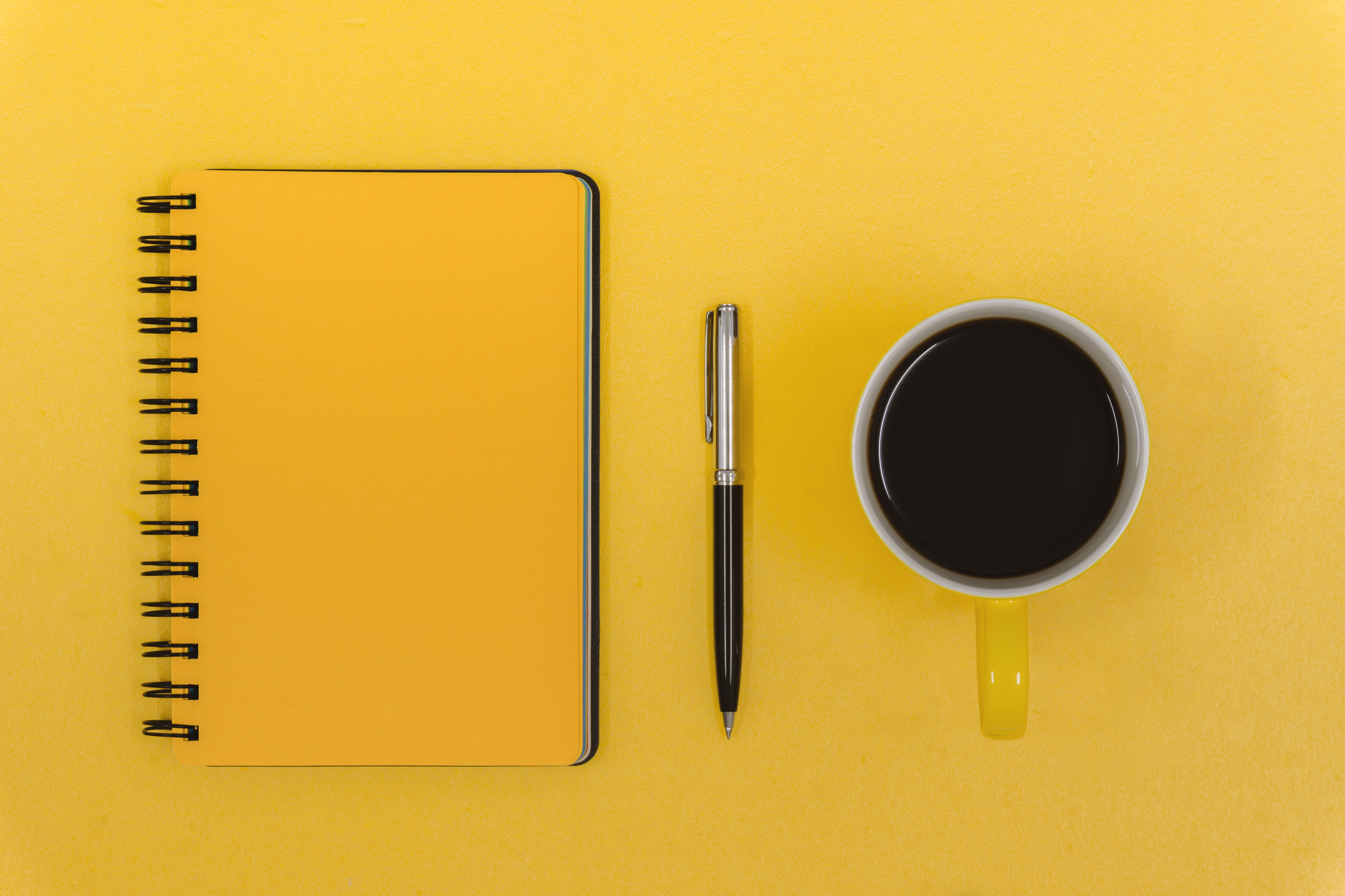 Notepad, Pen and Coffee Mug on Yellow Work Desk