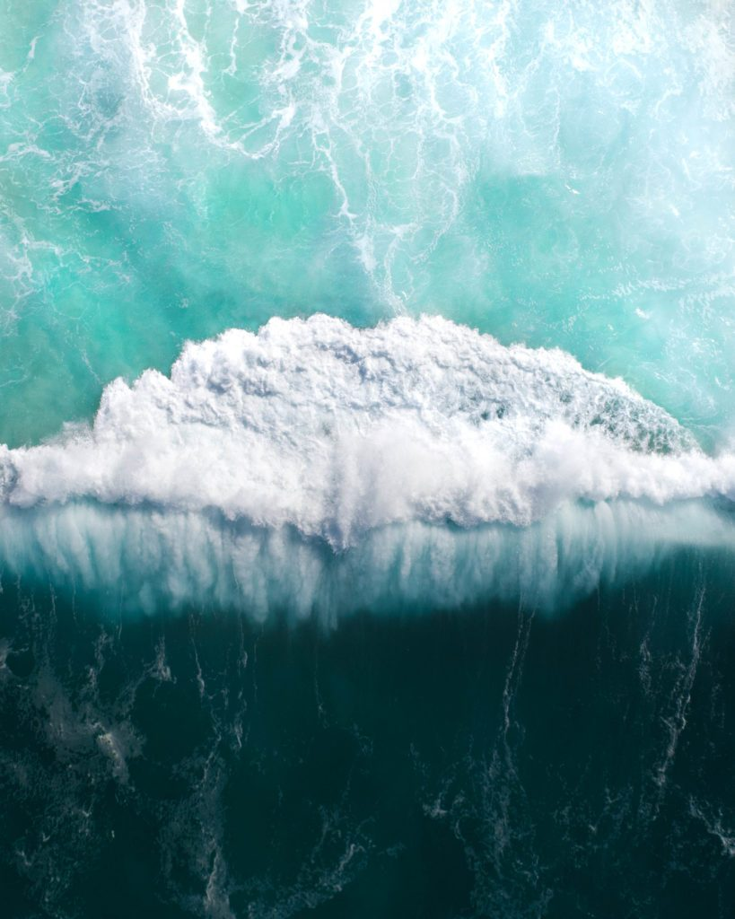 Top view of the ocean and a massive wave crashing. Storm wave breaking in the sea, ocean