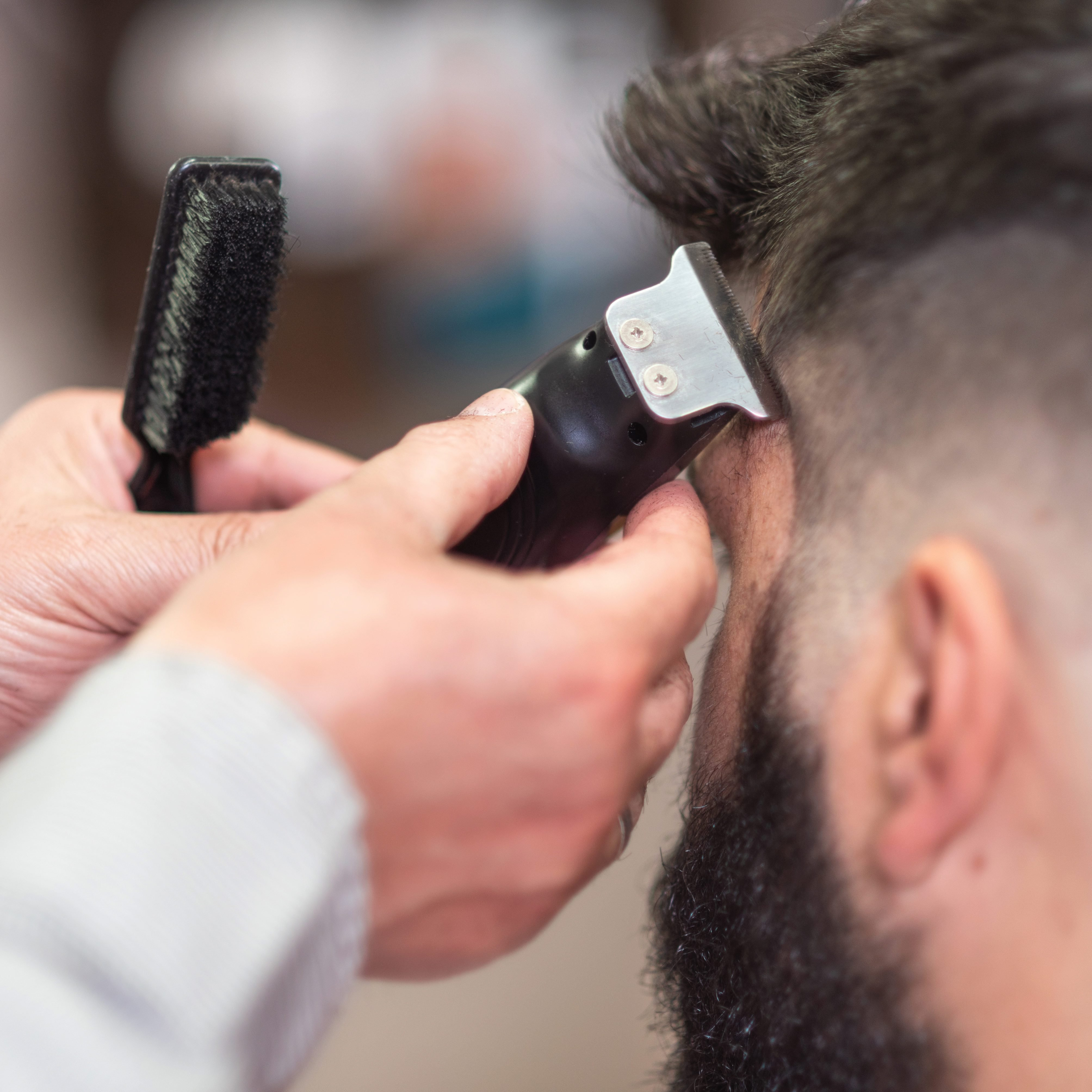 Cropped Hands Of Barber Cutting Male Customer Hair In Salon