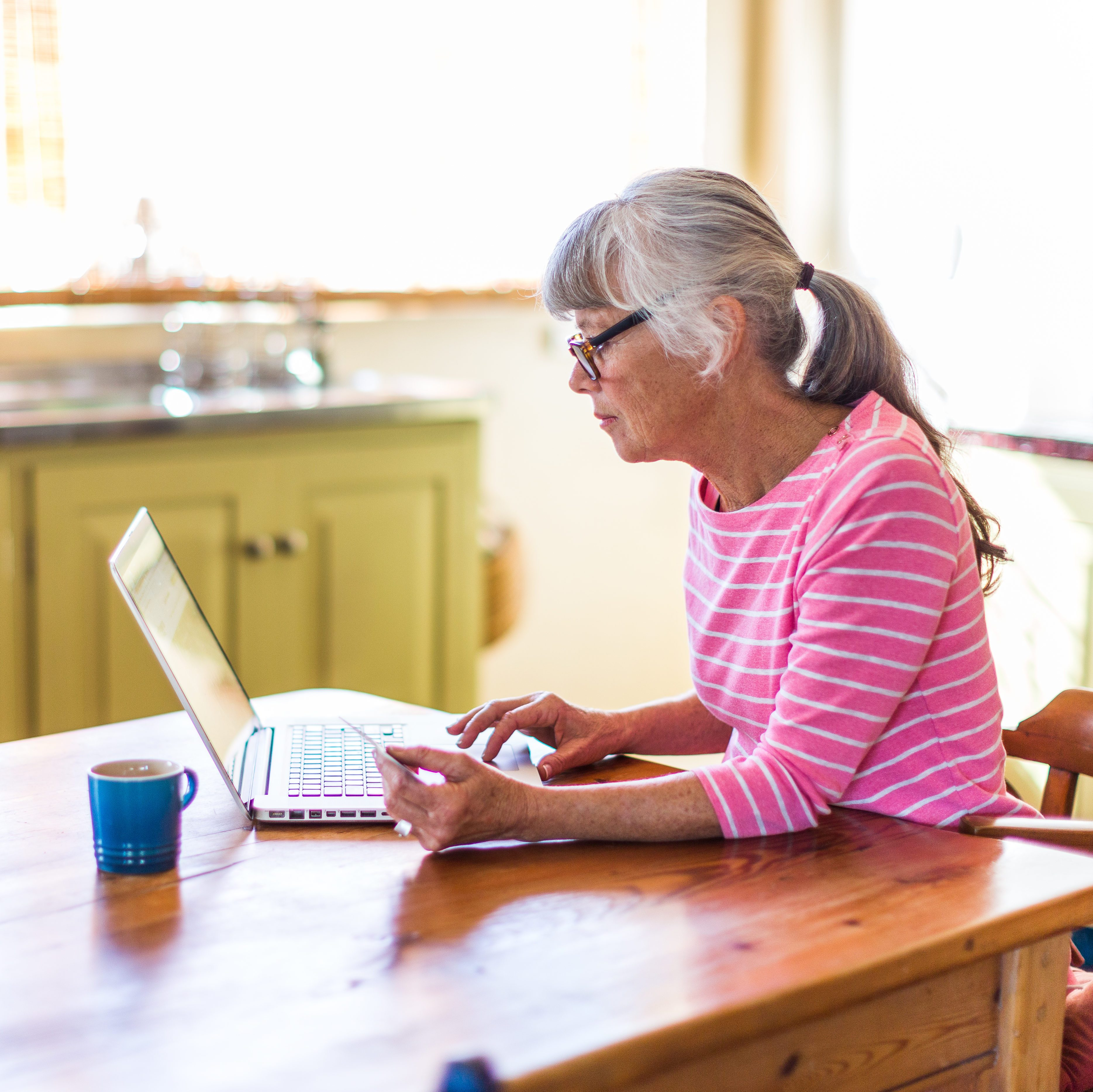 Senior woman shopping online with a credit card