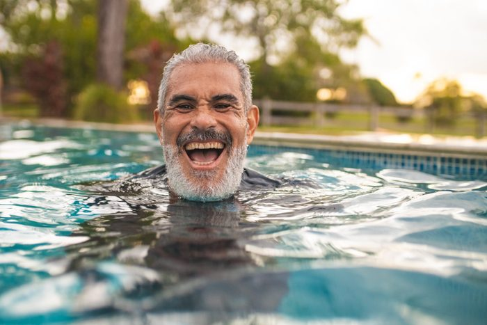 Senior man laughing in the pool