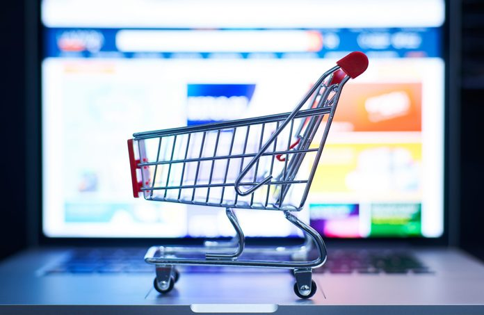 Close-Up Of Small Shopping Cart On Laptop