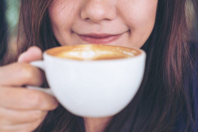 Midsection Of Woman Holding Coffee Cup