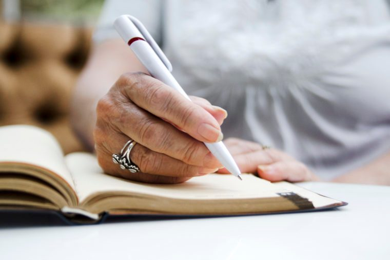 Senior woman writing with pencil on open note book.