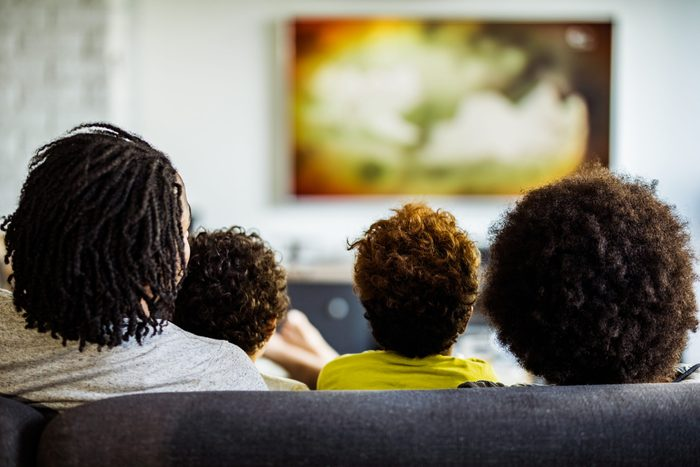 Back view of a family watching TV in the living room.