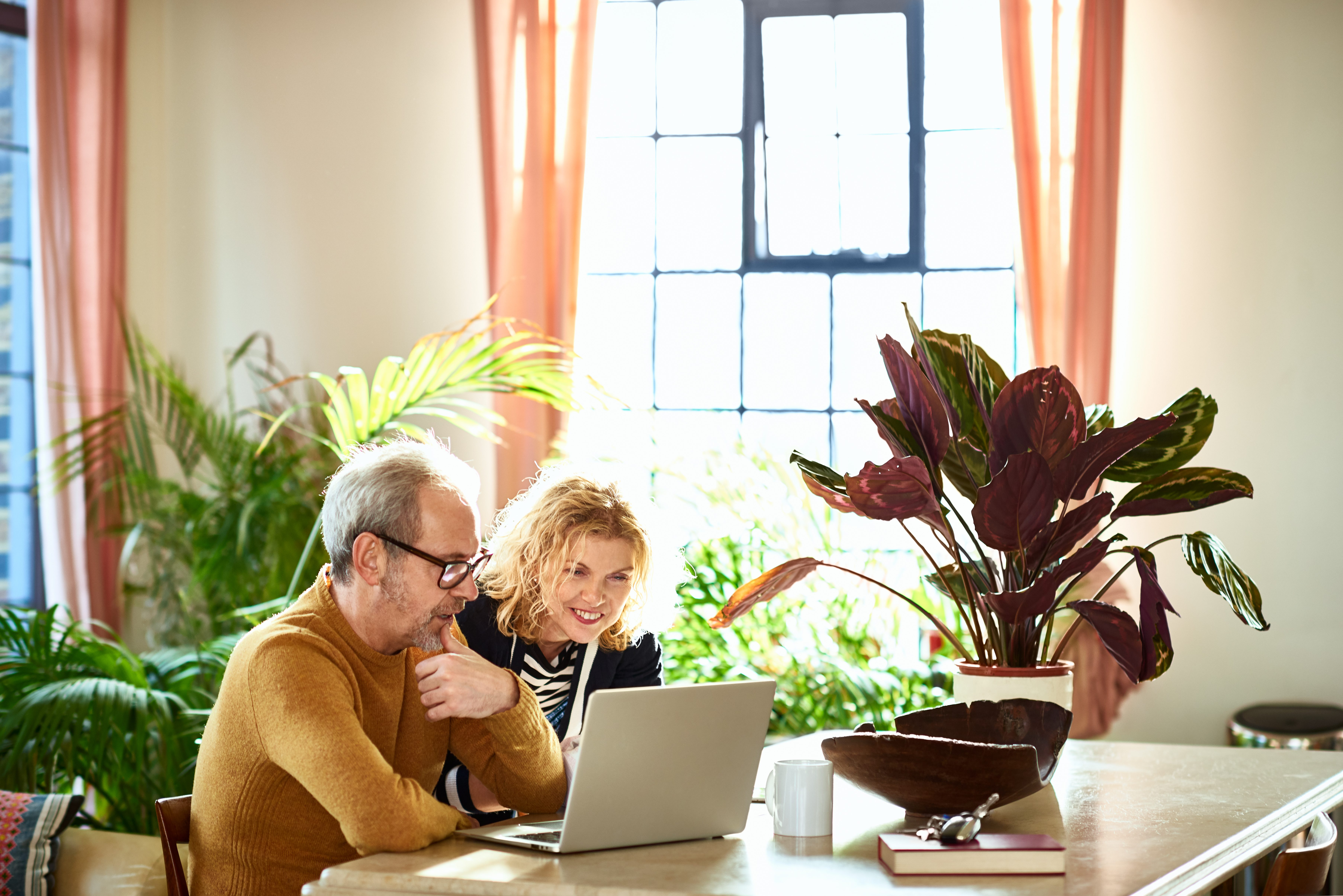 Excited mature woman looking at laptop with her husband