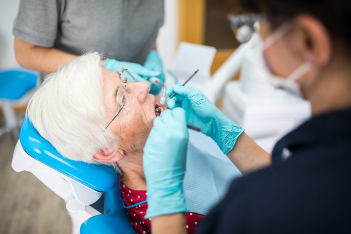 Dentist checking teeth of elderly female in clinic