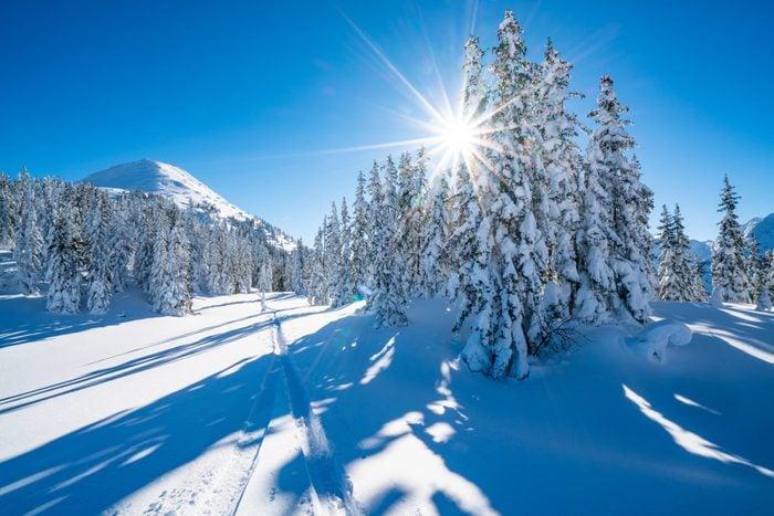 star shape sun in snowcapped winter mountain landscape