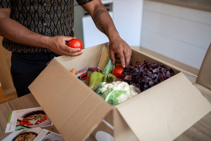 Latin Man Opening Parcel With Meal Kit
