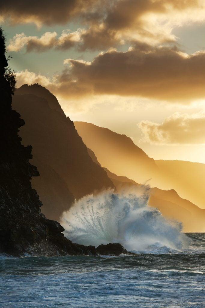 Surf smashing into Na Pali coast in Hawaii.