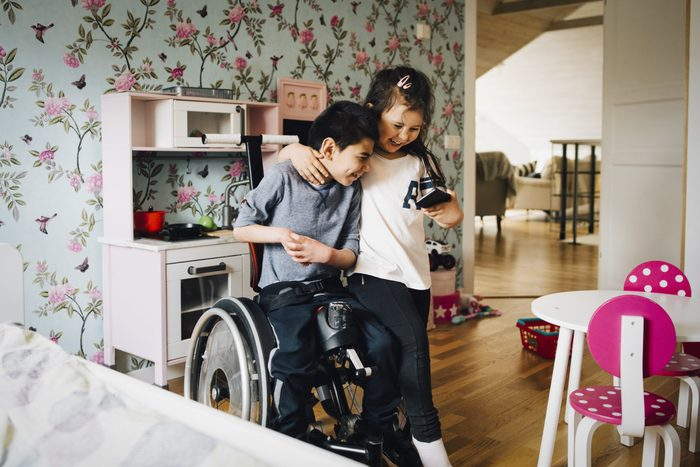 Cheerful sister watching video with autistic brother on mobile phone at home